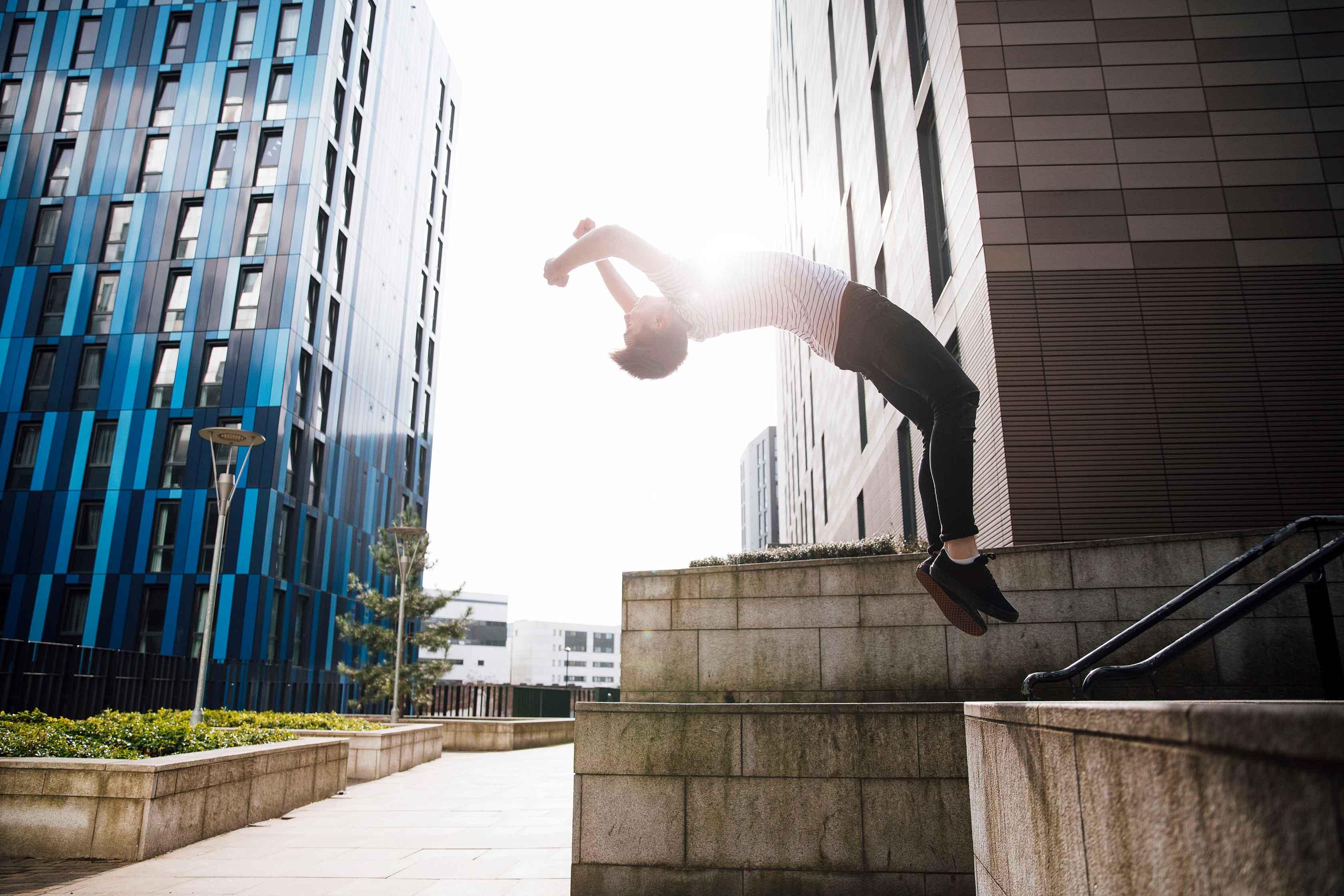 Hoppende person foran bygninger
