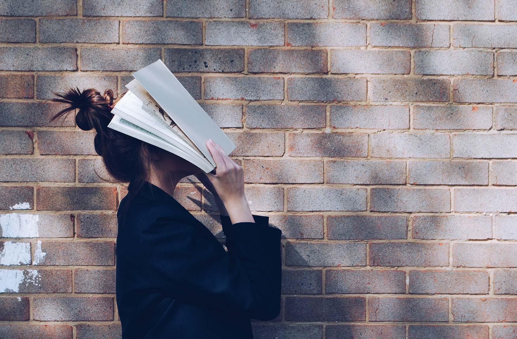 Ung jente med ansiktet i boka